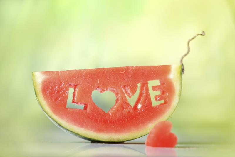 Fresh juicy watermelon slice on natural green background close-up with love letters word